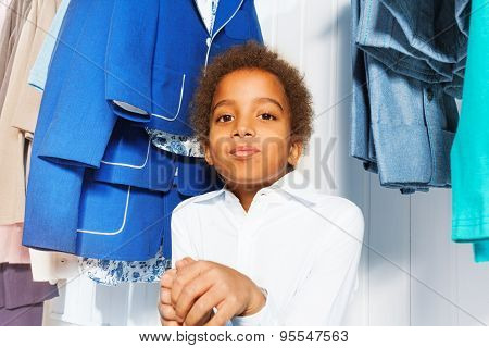 Cute African boy in white shirt sits under hangers