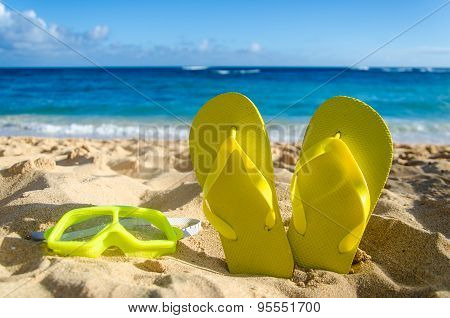 Yellow Flip Flops With Swim Glasses On The Sandy Beach