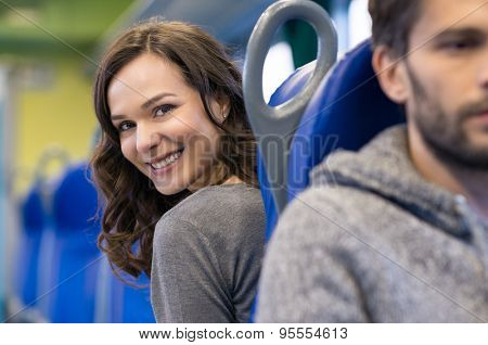 Portrait of a smiling young woman sitting in train. She is a brunette beautiful girl and she is looking back at camera. There are a row of blue seats in the coach.