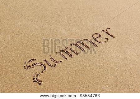 Summer - text written by hand on sand on a beach