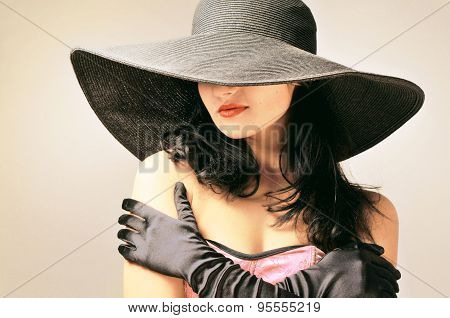Sensual woman in a black hat and black gloves