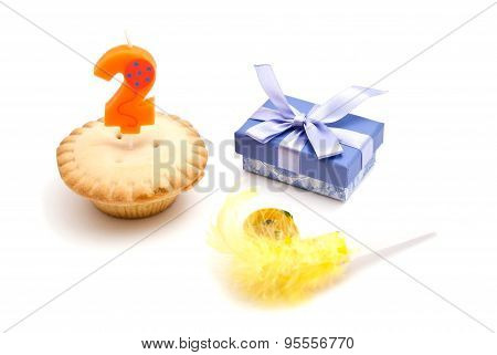 Cupcake With Two Years Birthday Candle, Gift And Whistle On White
