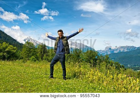 Full length of 20s man wearing dark jeans, navy top and gillet with arms out-stretched standing on grass. Snow-capped mountain vista and cloudy blue sky backdrop