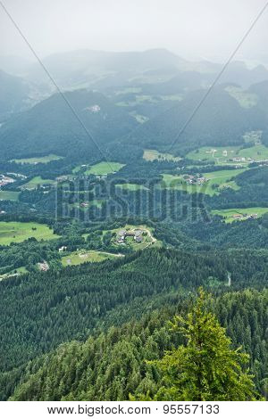 High angle view of misty mountain valley covered with green fir trees, patches of green fields also visible
