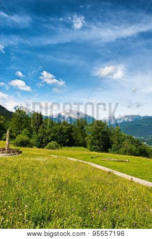 Footpath in the Berchtesgaden Alps in Germany crossing a lush green grassy plateau with a view to distant mountain peaks