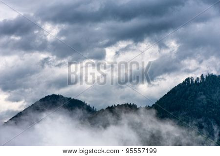 Scenic view of tree covered mountains beneath a moody cloudy sky, white mist in foreground