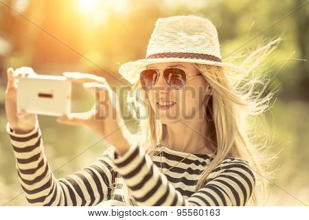 Portrait of blond photographing woman in white hat and sunglasses on the lake background.