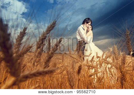 Young Bride And Groom In Wheat Field With Blue Sky
