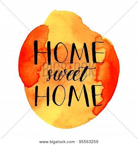 Home sweet home phrase handwritten on orange watercolor paint blot.