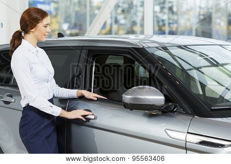 Young pretty woman dealer in showroom standing near car