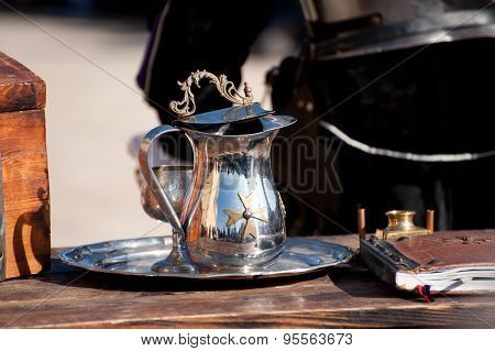 A Metal Pitcher With Maltese Cross