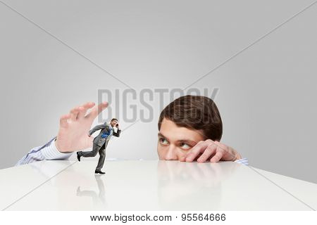 Young man looking from under table and catching running businessman