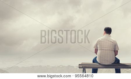 Fat man sitting on bench with his back and looking away