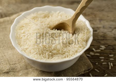 White Plate Of Long Grain Rice With Spoon On Wooden Background