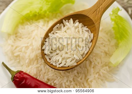 Long Grain Rice In A Wooden Spoon On A Background Plate, Green Salad, Chili Pepper. Healthy Eating,