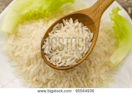 Long Grain Rice In A Wooden Spoon On A Background Plate, Green Salad. Healthy Eating, Diet, Vegetari
