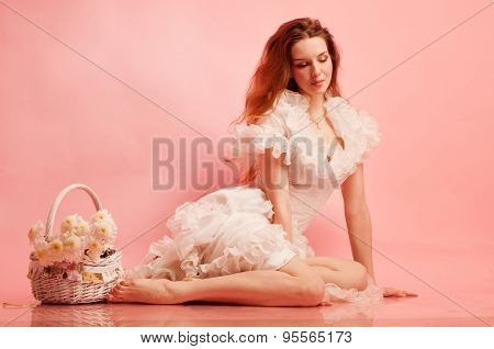Studio full length portrait of a young beautiful lady in white dress on a pink background