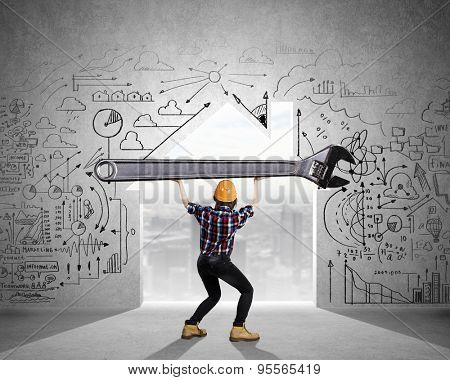 Young woman builder and keyhole at background lifting big key above head