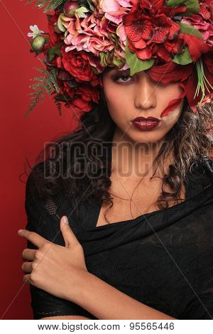 Beautiful Latina Woman With Floral Headpiece on Red Background