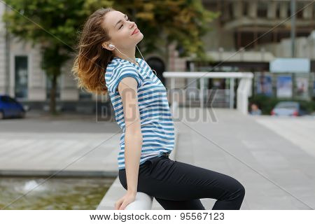Girl Listening To Music In The Background Of The City