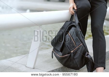 Girl Holding A Heavy Backpack In Her Hand
