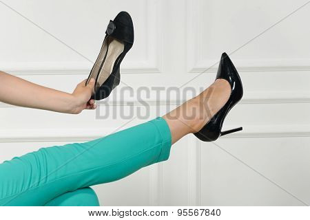 Woman Chooses Shoes With One Leg Up