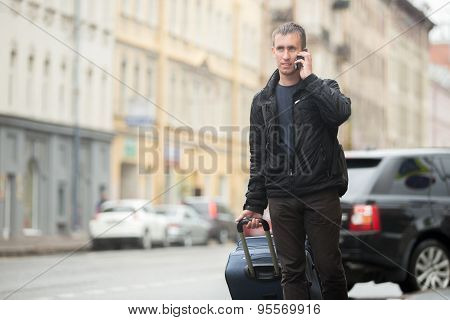 Young Traveler Talking On Mobile Phone In The Street