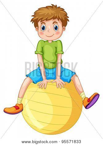 Little boy sitting on a yellow ball
