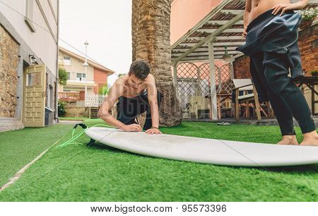 Surfer man with wetsuit waxing woman surfboard