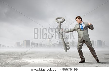 Angry businessman crashing stone key with punch