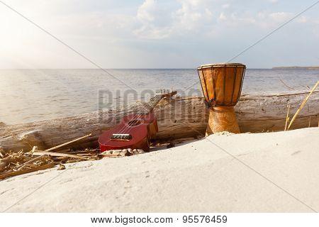 Ukulele & ethnic drum on a sunny beach.