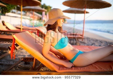 Young woman lying on sun lounger near the sea.Beach sunset and golden light.Woman in hat and bikini
