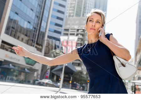 Businesswoman in a city street waving for taxi