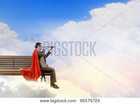 Super hero sitting on bench and looking in spyglass