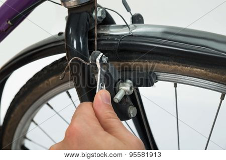 Person Hands Tightening Bolt Of Bicycle Tire