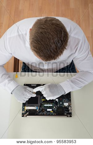 Man Repairing Laptop Motherboard