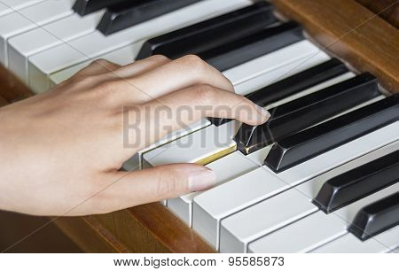 Girl's Left Hand Holding Pressed  Keys On A Piano