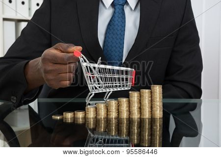 Businessman With Small Shopping Cart And Coins