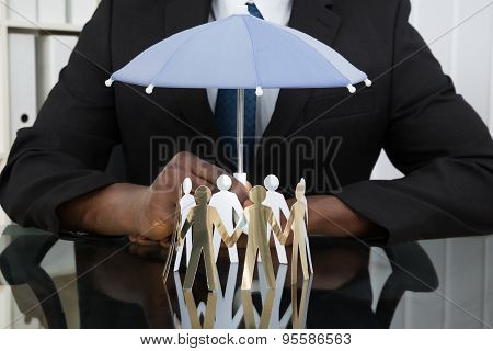 Businessman Holding Umbrella Over Paper Cutout People