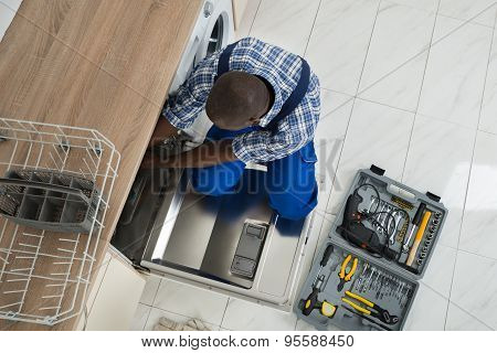 Repairman Repairing Dishwasher In Kitchen