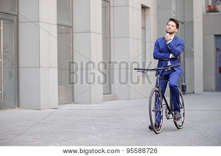 Handsome businessman riding his bicycle