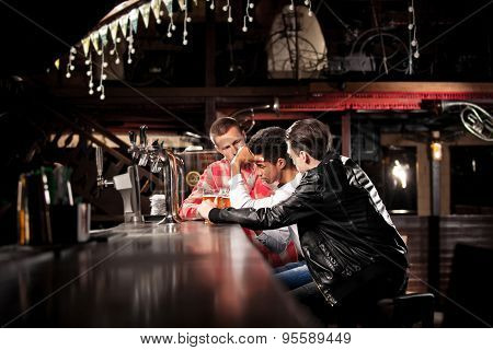 friends drink beer and spend time together in a bar.