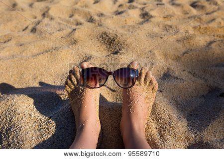 Luxury young woman legs and feet sunbathing on beach wearing sun glasses
