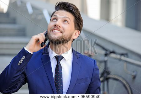 Nice businessman talking on mobile phone