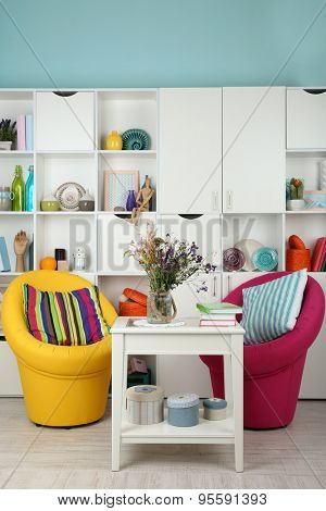 White living room with armchairs and bookcase