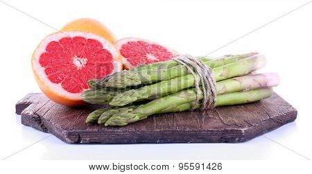 Fresh asparagus and grapefruit on cutting board isolated on white