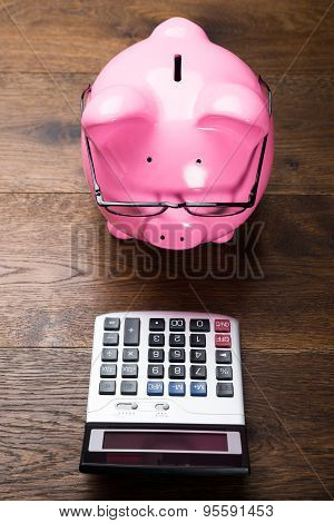 Piggybank With Calculator On Table
