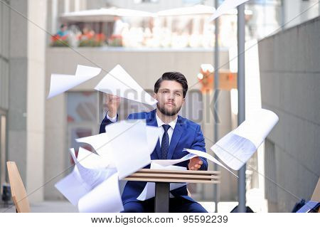 Serious man throwing papers out