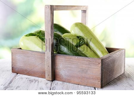 Fresh zucchini with squash and basil in wooden box on bright background