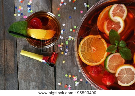 Sangria in bowl and glass on wooden table close up